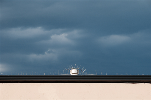 The edge of a rooftop against an oncoming storm.