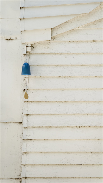 A blue wind chime hanging from a white clapboard wall.