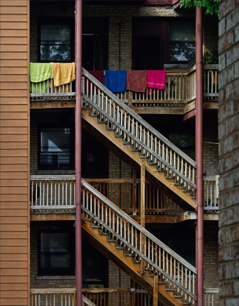 Colorful beach towels hanging from the railing of a third floor apartment.