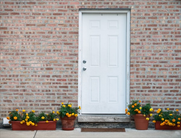 Marigolds in pots near a plain white door in a blank brick wall.