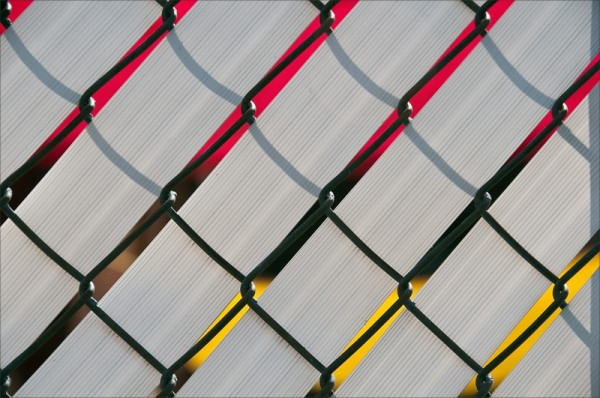 Bright red and yellow showing through gaps in a latticed fence.