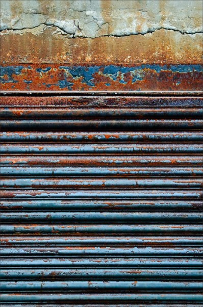 Horizontal lines of a colorful rusted door and concrete.