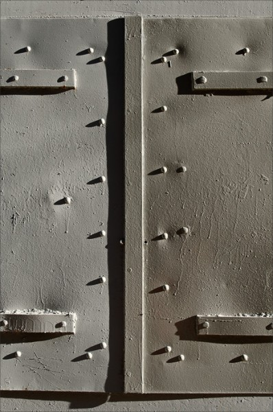 In morning sidelight, shadows play off the rivets of a metal door.