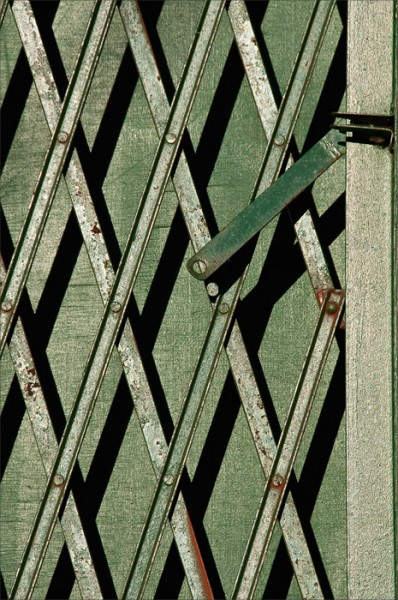In morning sidelight, shadows play off the lattice bars of a metal gate.